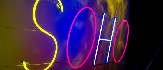A neon sign spelling Soho in yellow, pink and blue