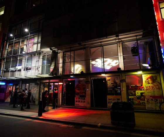The exteriror of a building shows a sloped ceiling with projections and red and blue lights emitting onto people walking along the pavement.