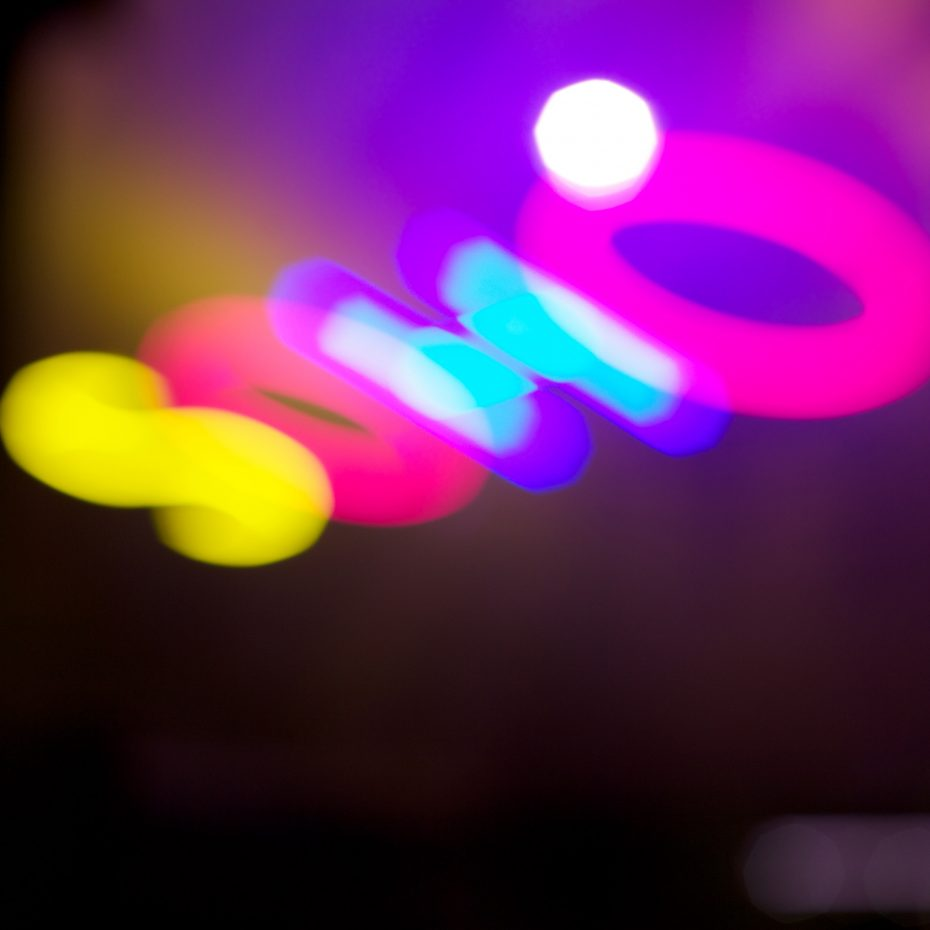 A blurred neon sign spelling out SOHO in yellow, blue and pink