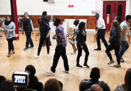 Teenager participating in an acting workshop in a community hall