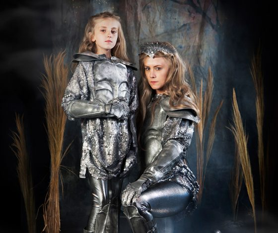 A blonde-haired women in a silver armor customer kneels next a girl, who is dressed the same way as her