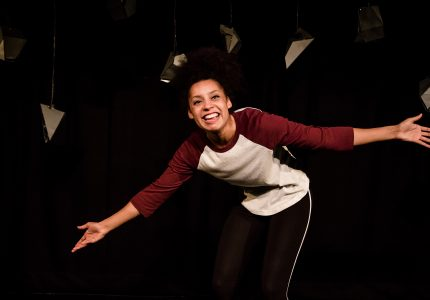 Young woman on stage with wide opens arms