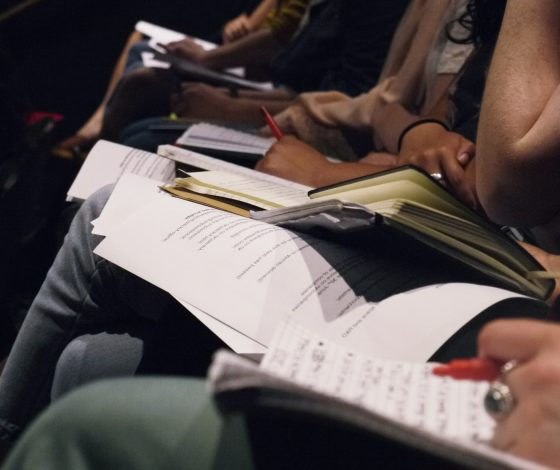 Scripts on a row of people's knees, some of whom are holding pens.
