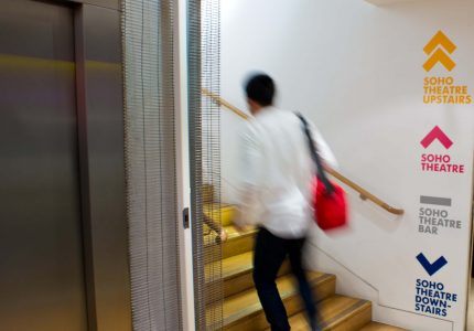 A young man in a white shirt with a red bag climbs the stairs next to directional signange explaining which theatre auditoirum is on which floor