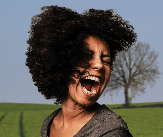 Woman with large hair screams with a rural scene behind her