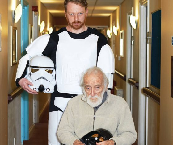 A stern looking man in a storm trooper costume, carrying the helmet in his right hand, pushes a sad-looking elderly man in as wheelchair down the corridor of a hospitalthe