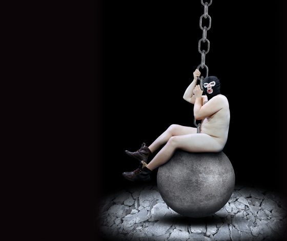 A naked man wearing a gimp mask swings on a wrecking ball