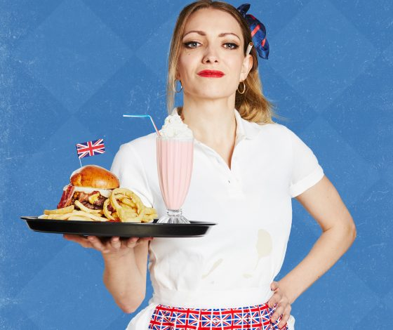 A young waitress in a dirty tshirt and union jack apron carries a milkshake and burger on a tray whilst smirking