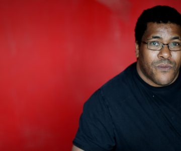 Roy Williams, playwright, in a black tshirt and glases, sitting against a red background