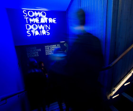 A blurred audience member walks down a blue-lit stairwell towards a neon sign saying Soho Theatre Downstairs.