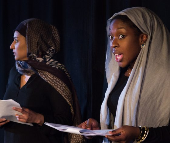 Two women wearing headscarves read from scripts