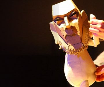 A cardboard puppet is control by two puppeteers
