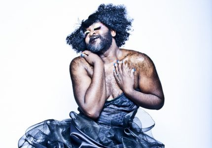 A full figured black man in a navy blue wig and beard ruffled bodice-dress swoons with his eyes closed