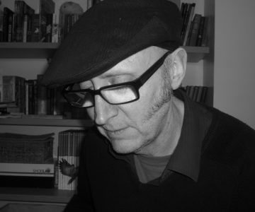 A man in glasses, a black flat cap, shirt and black jumper looks down from the camera in front of a bookcase