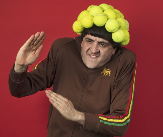 A man with a tennis ball hat and zip up sports tracksuit makes karate-style hand gestures and grimaces