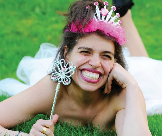 A young woman wearing a pink tiara is lying on grass, smiling widely