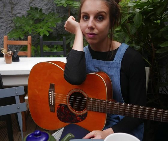 A young woman sits in an outdoor cafe leaning on a guitar rested on her lap, a pot of tea on the table in front of her.