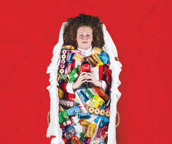 Man in coffin, surrounded by sympathy snacks on red background