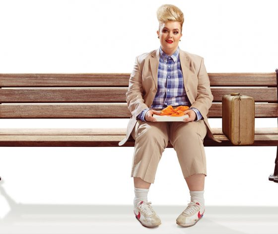 A woman dressed as Forrest Gump sits on a bench holding a box of chocolate