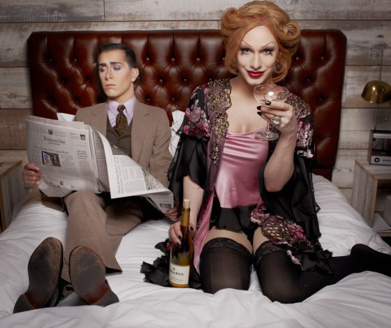 Man & woman on bed. Woman holding glass looking at camera. Man reading newspaper