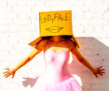 Woman wearing pink ballerina outfit with cardboard box on her head with LadyFace written on it and a drawn on pair of lips