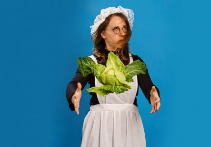 A young woman in a Victorian maid's outfit shakes her head and throws a cabbage in the air