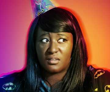 Woman looking confused wearing a party hat in front of a purple and orange background
