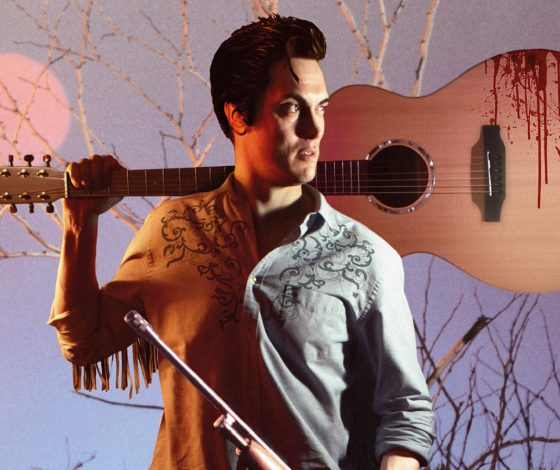 A young man with an Elvis Presley style quiff, holds a hold stained guitar over his shoulder and a shotgun in his hand