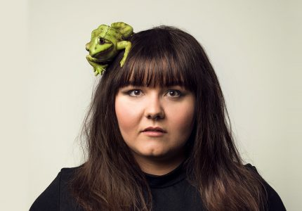 A young woman looks forward with a large green frog on her head