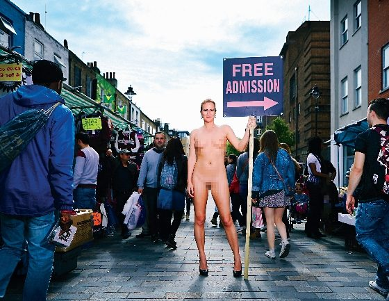 Woman stood naked in busy market hold a sign that reads 'Free Admission'