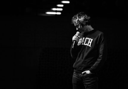 black and white image of James Rhodes side on in a dark hooded top, holding a microphone to his mouth and looking down