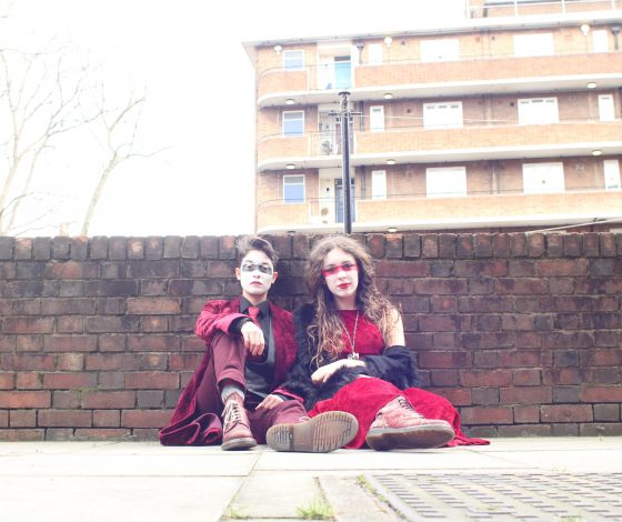 Two women dress in red clothing sat against a brick wall