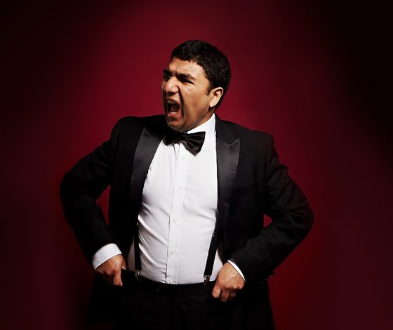 A man in a tuxedo with arms akimbo scowls comically to off-camera, dark red background