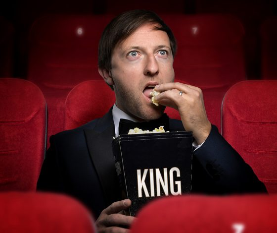 A man eats popcorn in a cinema