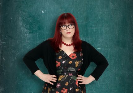 A red haired bespectacled woman poses with arms akimbo in front or a blackboard, slightly coy expression and glancing to the side