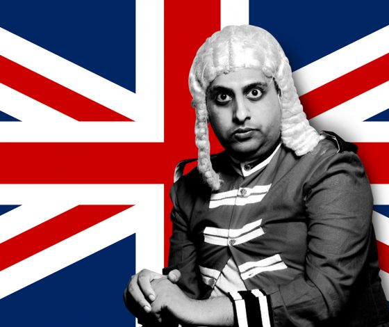 A man wears a wig and old British military clothing, in front of a Union Flag