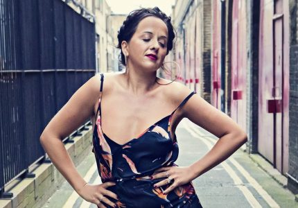 Luisa Omielan strides down a street towards camera with her arms akimbo and eyes closed