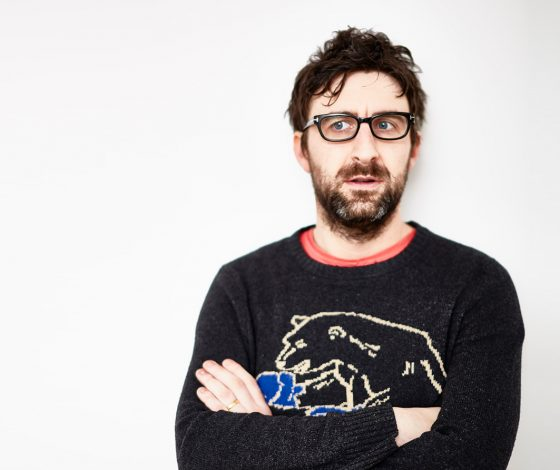 A man wearing glasses and jumper looks to the side