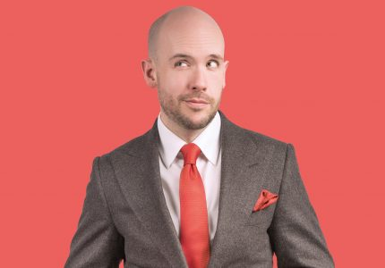 Tom Allen in a grey suit and red tie looks wryly to the side, light red backdrop