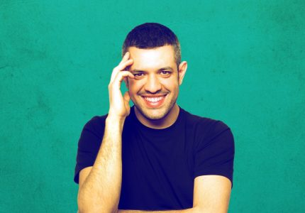 Francesco De Carlo smiles at camera touching his temple and folding the other arm against a turquoise