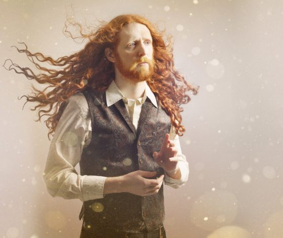Alasdair Beckett-King with flowing red hair wearing a patterned waistcoat and shirt gazes to the side, motes of light in the background and foreground