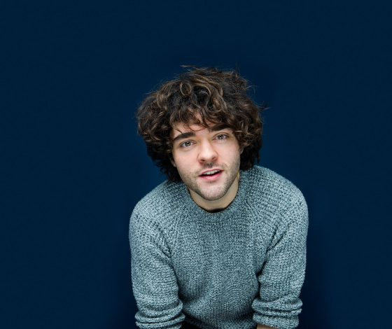 A young man with a light blue cable-knit jumper and brown curly hair smiles at the camera, dark blue background