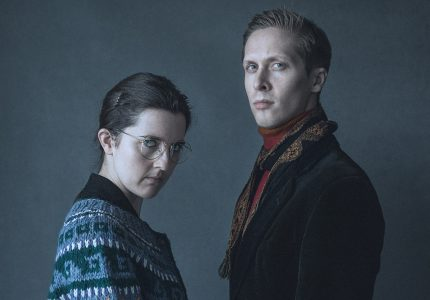 Rose and Will look moodily at the camera, dark blue backdrop. Rose wearing a patterned blue sweater and spectacles, Will wearing a suede jacket and scarf.