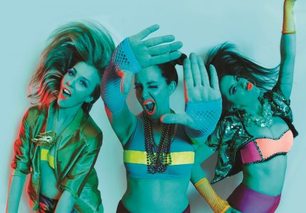Green saturated image of 3 young women in neon party attire striking hi-energy poses