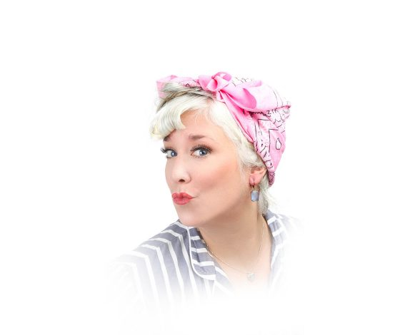 A woman with blight blonde hair and a pink headwrap, head turned slighlty, pouts, white background