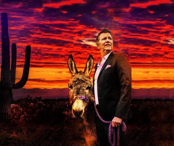 Stewart Francis, holding a donkey on a lead, looks into the distance in front of a sunset with a desert backdrop