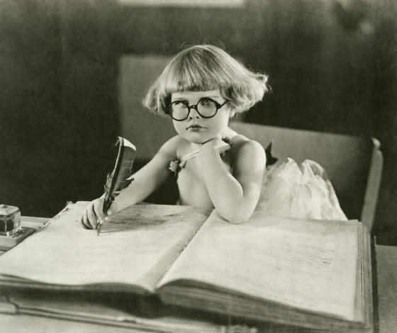 black and whitw prohograph of a toddler wearing glasses writing with a quill into a large book