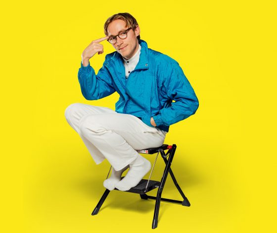 a bookish looking bespectacled man in a shellsuit top and white trouser sits perched atop a small step-ladder. Yellow background