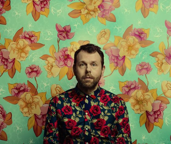 Michael Legge in a floral print shirt on a floral background