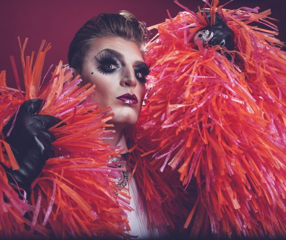 Reuben poses with a read feather boa and black leather gloves, wearing glam makeup
